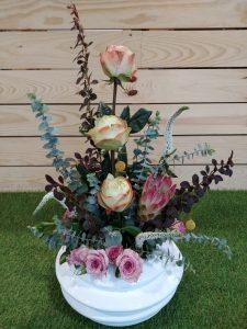 Centro de flores decorativo con rosas y verdes variados.
