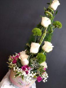 Cesta decorativa con bambú, rosas y flores variadas.