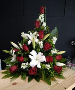 Centro en pico con rosas rojas y lilium.
