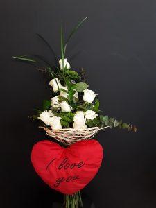 Ramo de flores con peluche de corazón.