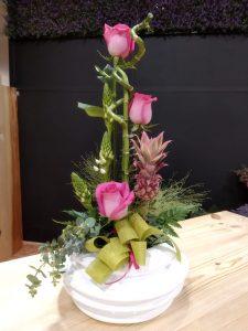 Centro de mesa decorativo con bambú, rosas, ananá y ornithogalum.