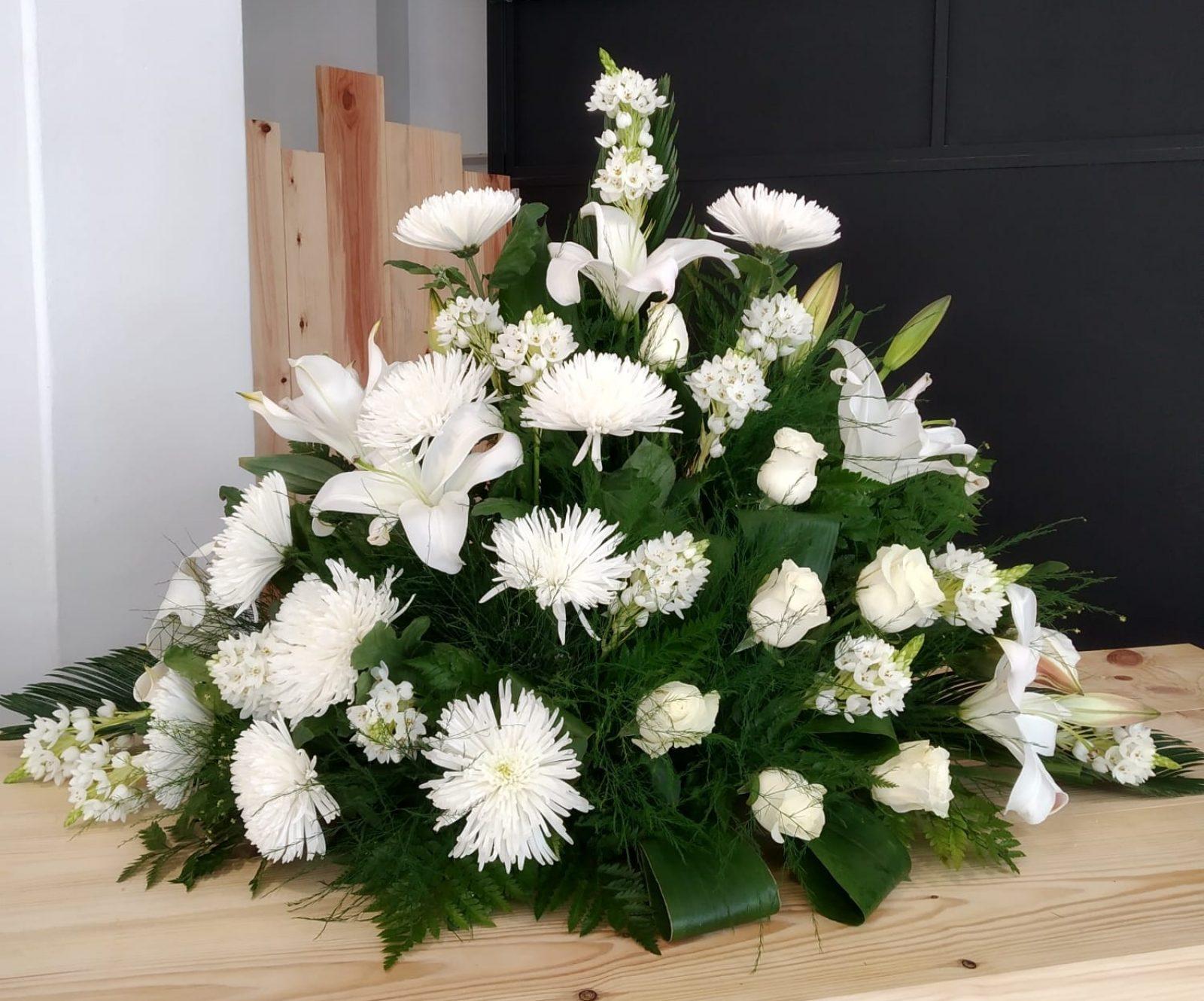 Centro en tono blanco con lilium, ornithogalum, uniflor y rosas.