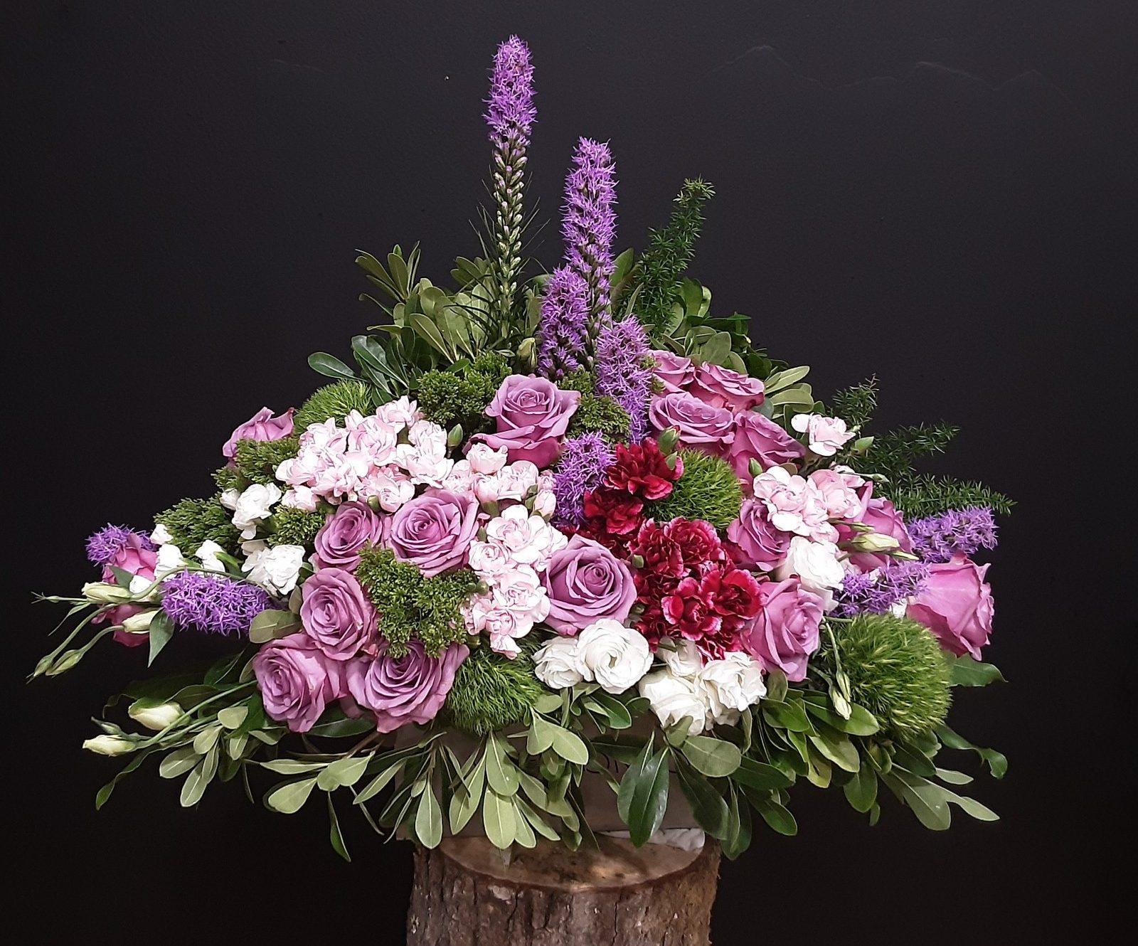 Centro de liatris y rosas en tonos granate y violeta.